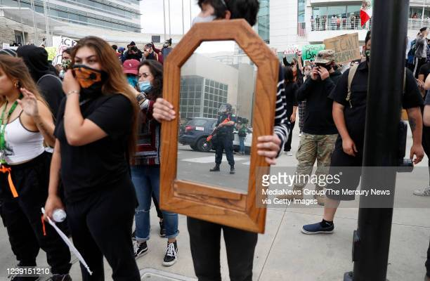 A protester holds a mirror during a protest of the killing of George Floyd outside of San Jose City Hall in downtown San Jose Calif on Sunday May 31...