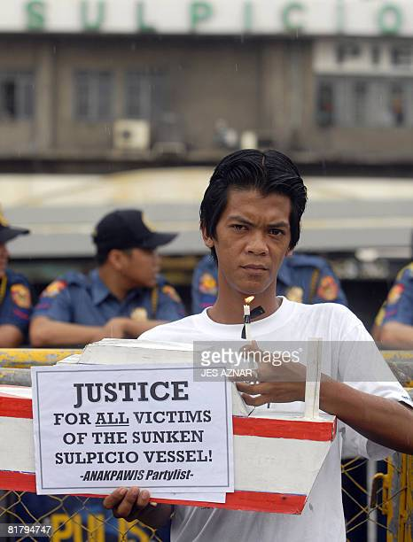 A protester holds a mock boat and a placard during a candlelight protest in front of the Sulpicio Lines office in Manila on July 2 2008 the owner of...