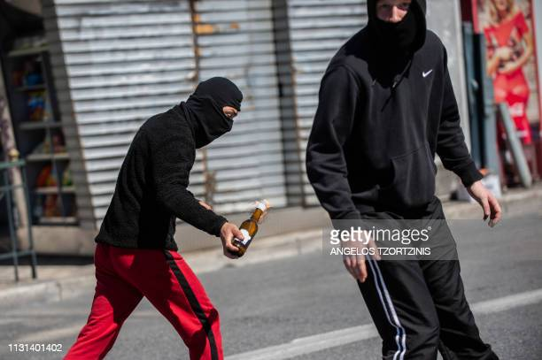 A protester holds a molotov cocktail during a demonstration against the reform plans over the university entrance system in Athens on March 18 2019
