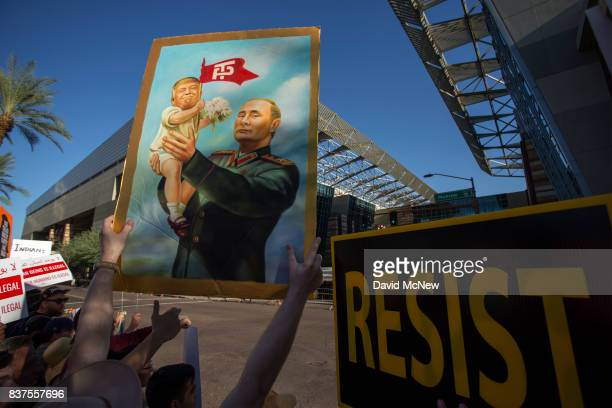 A protester holds a painting depicting President Donald Trump and Russian President Vladimir Putin outside the Phoenix Convention Center where a...