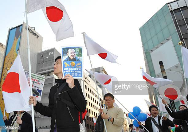 A protester holds a paper saying 'Free Liu Xiaobo' during an antiChina protest march in central Tokyo on November 6 2010 Japanese national flags...