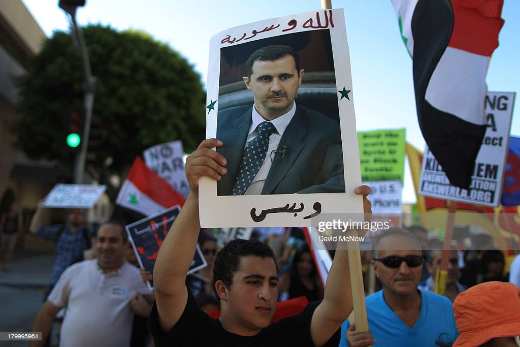 A protester holds a photo of Syrian president Bashar Hafez al-Assad at a march to urge Congress to vote against a limited military strike against the Syrian military in response to allegations that Assad has used sarin gas to kill civilians on September 7, 2013 in Los Angeles, California. The Obama administration claims to have clear evidence that the Syrian military broke international law by killing nearly 1,500 Syrian civilians, including at least 426 children, in a chemical weapons attack on August 21, and is seeking the support of Congress for a missile strikes to prevent future chemical weapons attacks by the regime and other nations.