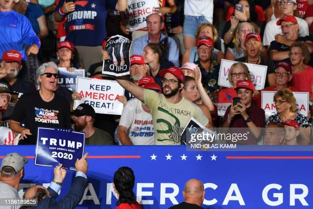 A protester holds a photo of US President Donald Trump with Jeffrey Epstein the financier accused of sexually abusing young girls and reading child...