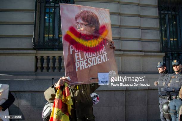 A protester holds a picture depicting former Catalan president Carles Puigdemont cross out with the Spanish flag colors near the Supreme Court during...
