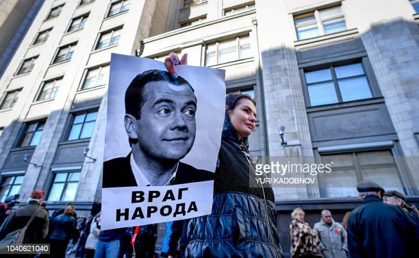 TOPSHOT A protester holds a picture of Russian Prime Minister Dmitry Medvedev bearing an inscription readin An enemy of people during a rally against...