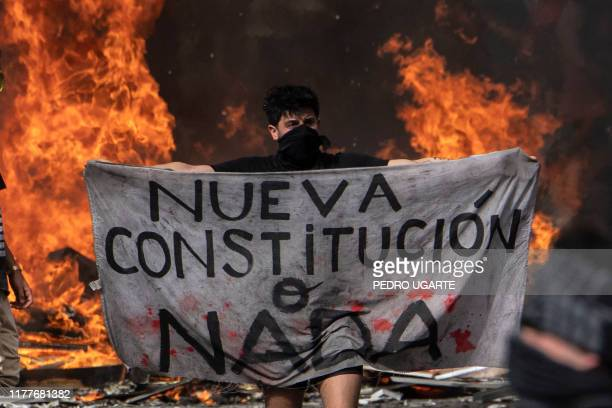 """Protester holds a piece of cloth reading """"New Constitution or Nothing"""" during a demonstration at Plaza Italia in Santiago, on the fifth straight day..."""