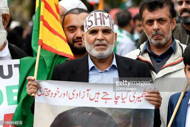 A protester holds a placard and a flag during the demonstration Kashmir protesters gathered at Parliament Square to demand the stop of the Indian...