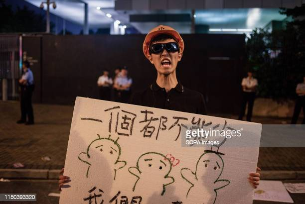 A protester holds a placard and shouts slogan against the Hong Kong government during the demonstration Despite the Chief Executive Carrie Lam's...