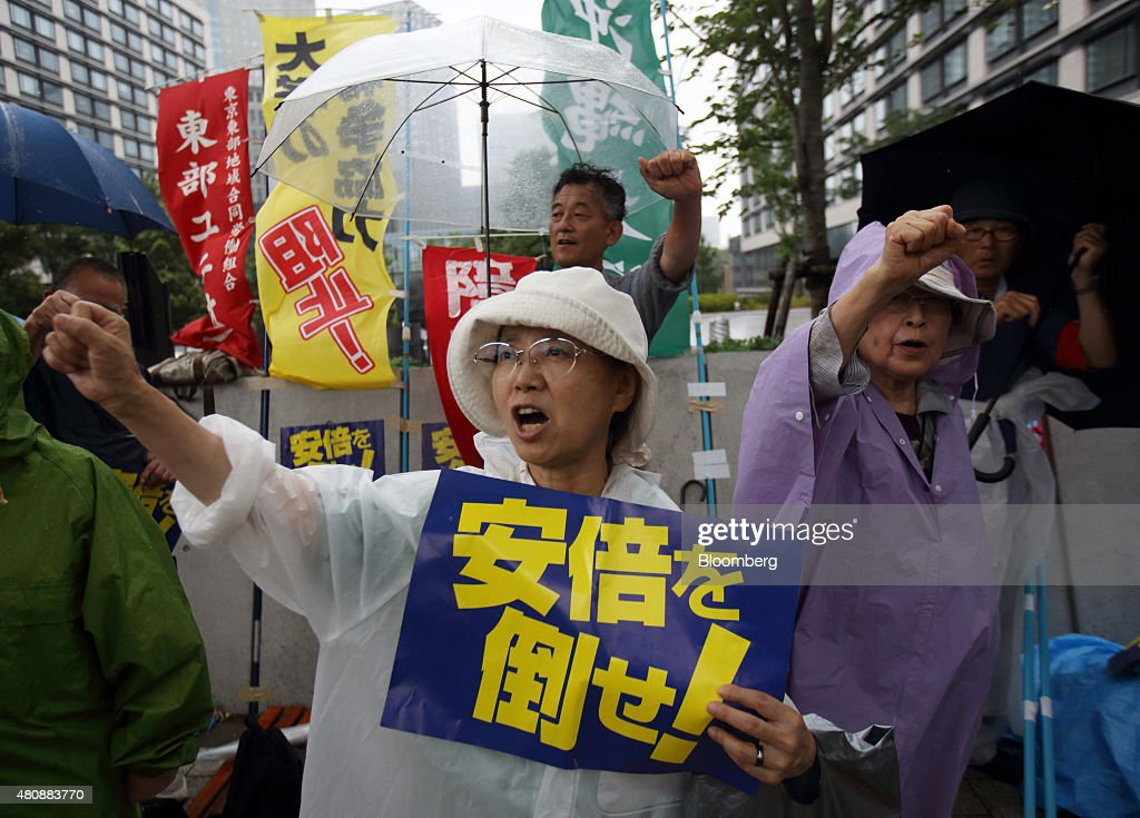 A protester holds a placard and shouts slogans during a rally against the security bills outside the National Diet building in Tokyo, Japan, on Thursday, July 16, 2015. Japanese Prime Minister Shinzo Abe's security bills passed parliament's lower house Thursday after a night of noisy protests, as his push to expand the role of the military risks further eroding his public support. Photographer: Tomohiro Ohsumi/Bloomberg via Getty Images