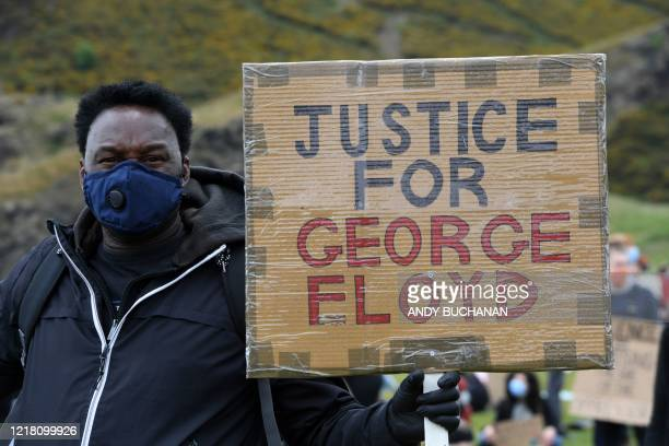 A protester holds a placard as he attends a demonstration in Edinburgh on June 7 organised to show solidarity with the Black Lives Matter movement in...