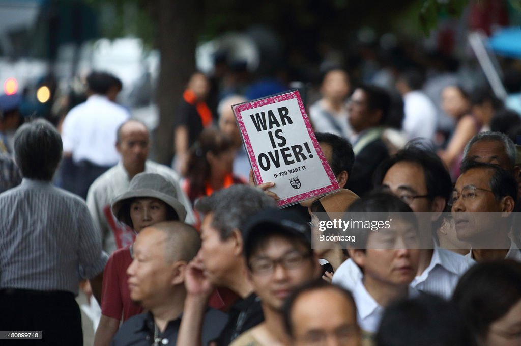 A protester holds a placard as he takes part in a rally against the security bills outside the National Diet building in Tokyo, Japan, on Thursday, July 16, 2015. Japanese Prime Minister Shinzo Abe's security bills passed parliament's lower house Thursday after a night of noisy protests, as his push to expand the role of the military risks further eroding his public support. Photographer: Tomohiro Ohsumi/Bloomberg via Getty Images