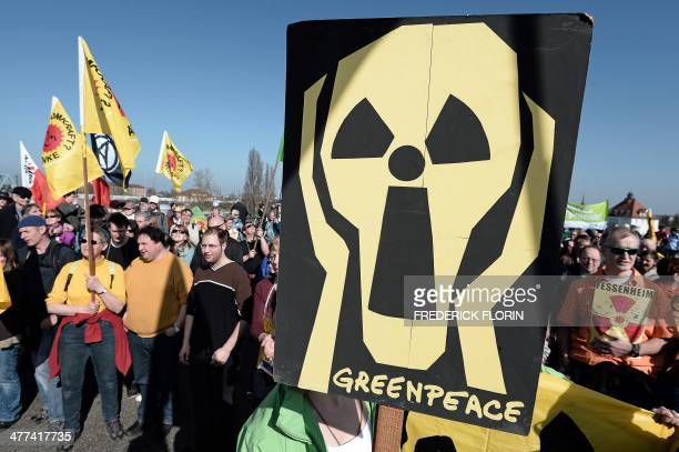 A protester holds a placard depicting Edvard Munch's painting 'The Scream' with a nuclear symbol during a demonstration of French and German...