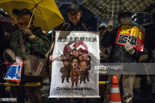 A protester holds a placard during a demonstration against Japan's Prime Minister Shinzo Abe after allegations of corruption on March 16 2018 in...