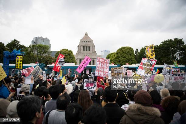 Protester holds a placard during a demonstration against Japan's Prime Minister Shinzo Abe after allegations of corruption calling him to resign on...