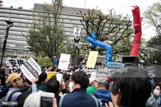 Protester holds a placard during a demonstration against the Japan's Prime Minister Shinzo Abe after allegations of corruption and calling him to...