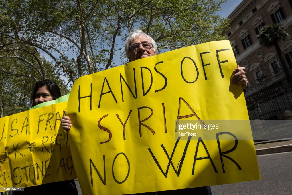 A protester holds a placard during a demonstration against the military action in Syria in front of the US embassy in Rome, Italy, 14 April 2018. USA, Britain and France launched airstrikes targeting three sites allegedly related to the Syrian government's chemical weapon capabilities. on April 14, 2018 in Rome, Italy
