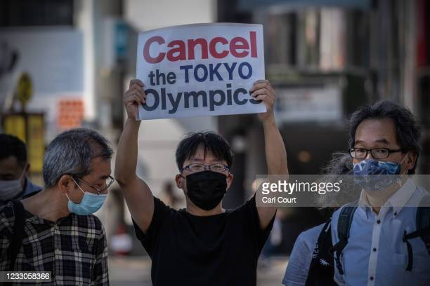 Protester holds a placard during a demonstration against the forthcoming Tokyo Olympic Games on May 23, 2021 in Tokyo, Japan. IOC vice president John...