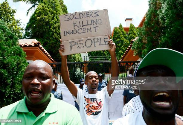 A protester holds a placard during a demonstration of Zimbabwean citizens outside the Zimbabwean Embassy in Pretoria on January 16 following the...