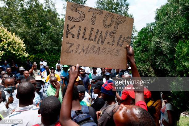 Protester holds a placard during a demonstration of Zimbabwean citizens outside the Zimbabwean Embassy in Pretoria on January 16 following the...