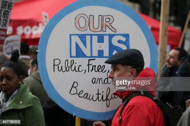 A protester holds a placard during a march against private companies' involvement in the National Health Service and social care services provision...