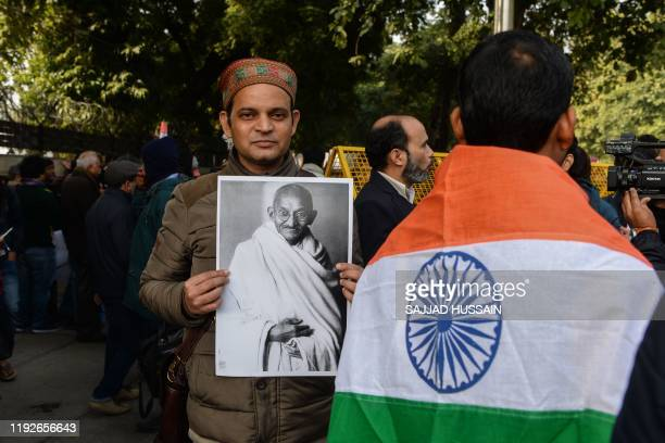 A protester holds a placard featuring Indian independence icon Mahatma Gandhi at a demonstration against India's new citizenship law and against an...