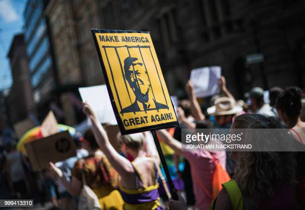 TOPSHOT A protester holds a placard featuring US President Donald Trump behinid bars during the socalled 'Helsinki Calling' march towards the Senate...