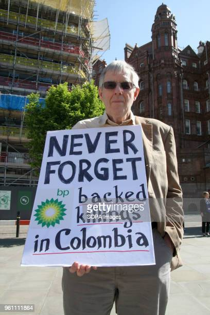 Protester holds a placard highlighting the Petroleum Company BP'S questionable practices in Colombia during a demonstration outside BP's AGM The...