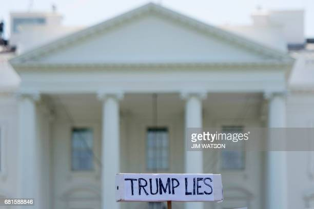 A protester holds a placard in front of the White House during a protest demanding an independent investigation in the Trump/Russia ties after the...