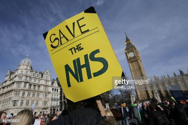 A protester holds a placard in support of the NHS in front of the Elizabeth Tower also known as Big Ben at the Houses of Parliament during a march...