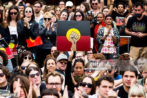 A protester holds a placard of a clenched fist on a Aboriginal flag during a protest organized by Aboriginal rights activists on Australia Day in...