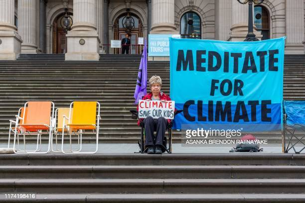 TOPSHOT A protester holds a placard outside the Victoria state parliament building to mark the beginning of the Extinction Rebellion protests in...