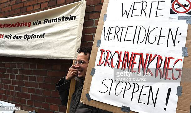 """Protester holds a placard reading """"Defend virtues, stop the drone war"""" in front of the Administrative Court where three Yemenis take legal action..."""