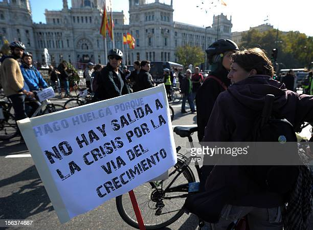"""Protester holds a placard reading """"I am on strike because there is no way out of the crisis through growth"""" during a general strike on November 14,..."""