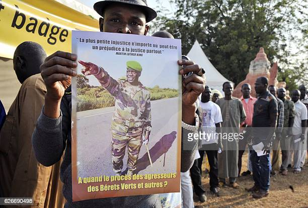 A protester holds a placard reading 'Injustice anywhere is a threat to justice everywhere' and 'When will there be a trial for the aggressors of the...