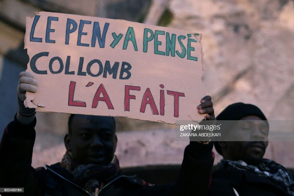 A protester holds a placard reading 'Le Pen thought of it, Collomb did it' on the Place Saint-Michel in Paris on February 21, 2018, during a demonstration against the French government's new immigr...