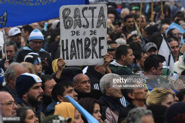 A protester holds a placard reading 'No More Hunger' during a demonstration against the government of President Mauricio Macri and the latest deal...