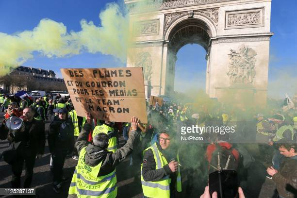 A protester holds a placard reading quotfeathers and tar for the medias anf the team of Macronquot during a Yellow vest antigovernment demonstration...