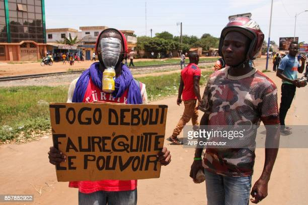 A protester holds a placard reading 'Togo standing Faure leave power' as supporters of opposition parties confront Togolese Security Forces during a...