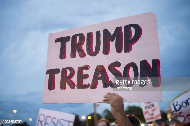 A protester holds a placard reading 'Trump Treason' following a rally with US President Donald Trump in Tampa Florida US on Tuesday July 31 2018...