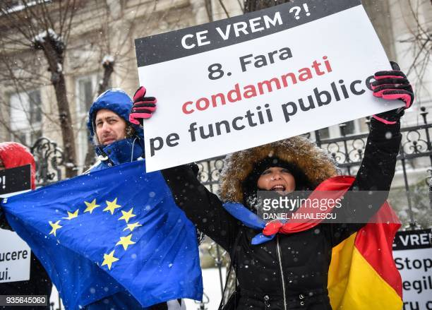 A protester holds a placard reading 'We don't want condemned people in public service' in front of the High Court of Cassation and Justice in...