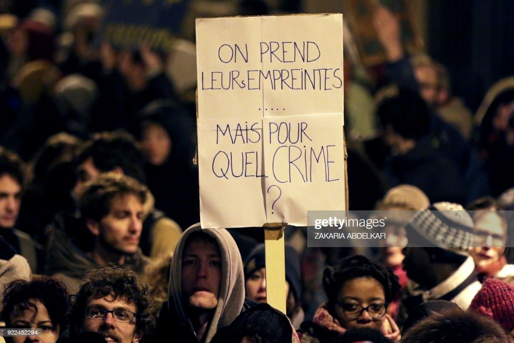 A protester holds a placard reading 'We take their fingerprints... but for what crime ?' in Paris on February 21, 2018, during a demonstration against the French government's new immigration bill. The French government defended a new immigration bill as 'completely balanced' on February 21 despite criticism from rights groups and some ruling party lawmakers that it will lead to thousands of extra deportations. The draft law, which criminalises illegal border crossings and speeds up procedures to deport economic migrants, was presented to the cabinet of President Emmanuel Macron for the first time. PHOTO / Zakaria ABDELKAFI