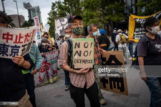 Protester holds a placard saying during a protest against the Tokyo Olympics on May 09, 2021 in Tokyo, Japan. With less than 3 months remaining until...