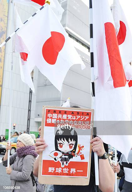 A protester holds a placard saying 'Free Asia' during an antiChina protest march in central Tokyo on November 6 2010 Japanese national flags...