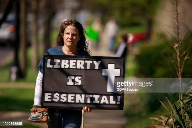 Protester holds a placard saying Liberty is essential during the demonstration. Protesters gather outside Indiana Governor Eric Holcomb's mansion in...