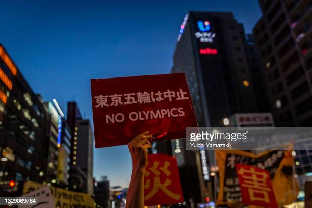 Protester holds a placard saying 'No Olympics' during a demonstration against the forthcoming Tokyo Olympic Games on July 16, 2021 in Tokyo, Japan....