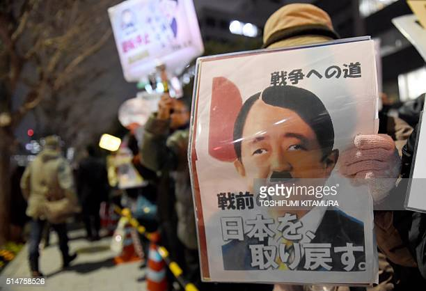 A protester holds a placard showing a caricature of Japanese Prime Minister Shinzo Abe in the likeness of Adolf Hitler during an antinuclear...