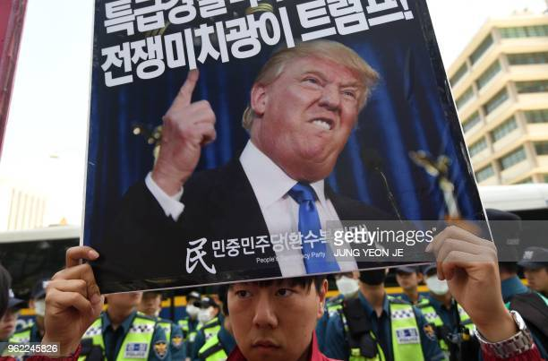 TOPSHOT A protester holds a placard showing a picture of US President Donald Trump during an antiTrump rally near the US embassy in Seoul on May 25...