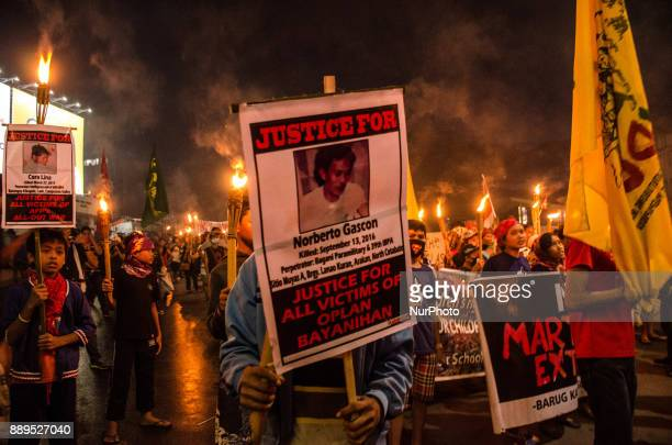 A protester holds a placard showing a victim of the Armed Forces of the Philippines' war at Bonifacio Shrine in Manila on 10 December 2017 to show...