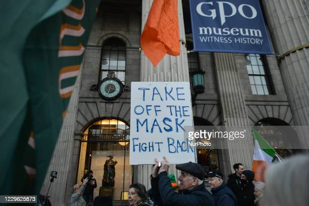 Protester holds a placard stating 'Take Off The Mask, Fight Back' outside the GPO on OConnell Steet during an anti-lockdown rally. On Saturday,...