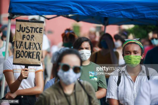 Protester holds a placard that says Justice for Vauhxx Booker during a community protest against racism. Protesters are demanding justice for Vauhxx...